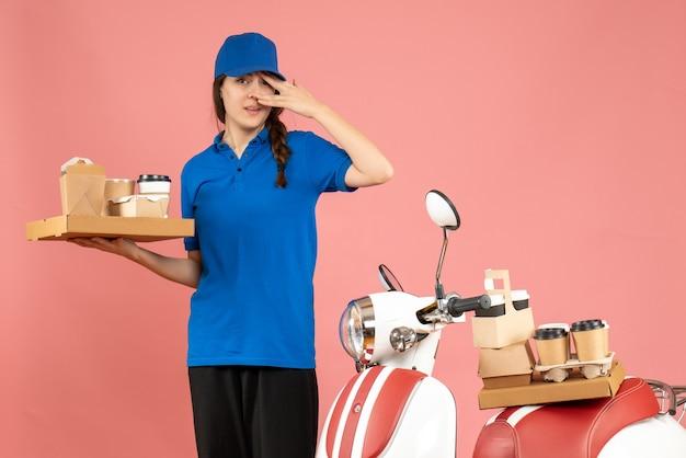 Vorderansicht des kuriermädchens, das neben dem motorrad steht und kaffee und kleine kuchen auf pastellfarbenem pfirsichhintergrund hält