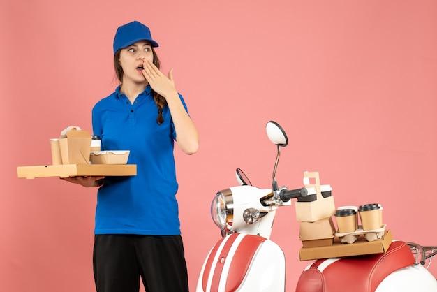 Vorderansicht des kuriermädchens, das neben dem motorrad steht und kaffee und kleine kuchen hält und sich auf pastellfarbenem pfirsichhintergrund überrascht fühlt
