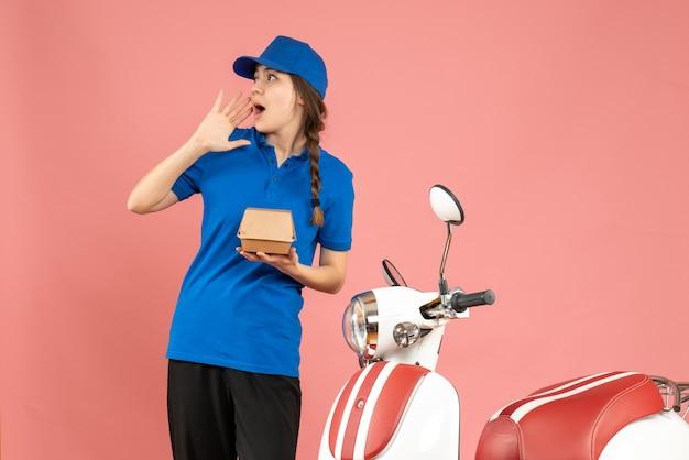 Vorderansicht des kuriermädchens, das neben dem motorrad steht und kuchen hält, konzentriert sich auf etwas auf pastellfarbenem hintergrund in pfirsichfarbe