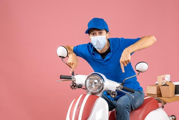 Vorderansicht des kuriermannes in medizinischer maske mit hut, der auf dem roller sitzt und auf pastellfarbenem pfirsichhintergrund nach unten zeigt