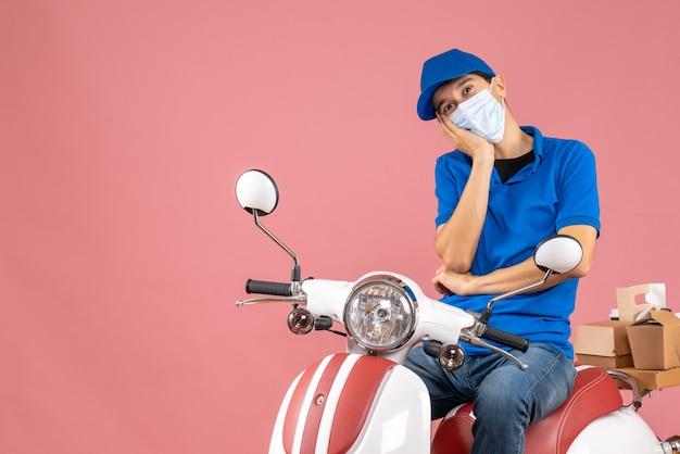 Vorderansicht des kuriermannes in medizinischer maske mit hut, der auf dem roller sitzt und etwas mit hoffnungsvollem gesichtsausdruck auf pastellfarbenem pfirsichhintergrund betrachtet