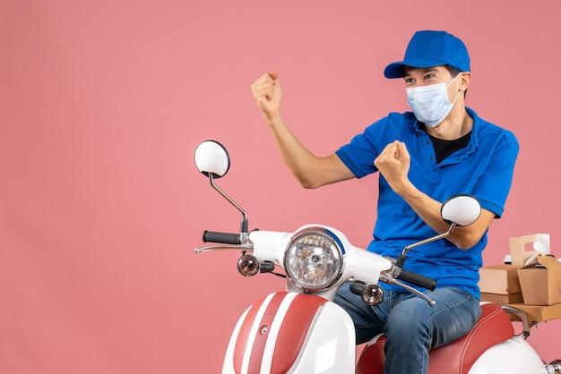 Vorderansicht des kuriermannes in medizinischer maske mit hut, der auf dem roller sitzt und seine kraft auf pastellfarbenem pfirsichhintergrund zeigt