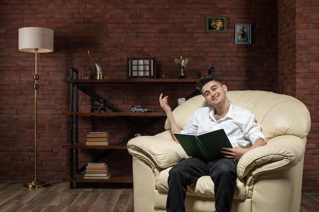 Vorderansicht des lächelnden jungen mannes, der auf sofa sitzt und notizen innerhalb des arbeitsbüros des raumgeschäftsarbeitsmöbelhauses schreibt