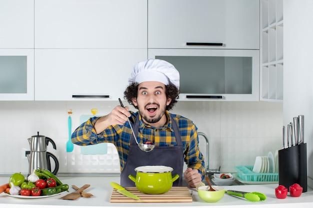 Vorderansicht des lächelnden kochs mit frischem gemüse, das fertiggerichte in der weißen küche schmeckt
