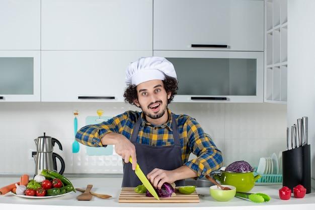 Vorderansicht des lächelnden kochs mit frischem gemüse, das lebensmittel in der weißen küche hackt