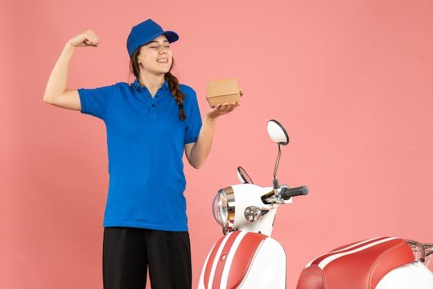 Vorderansicht des lächelnden kuriermädchens, das neben dem motorrad steht und kuchen hält, der muskulös auf pastellfarbenem pfirsichhintergrund zeigt