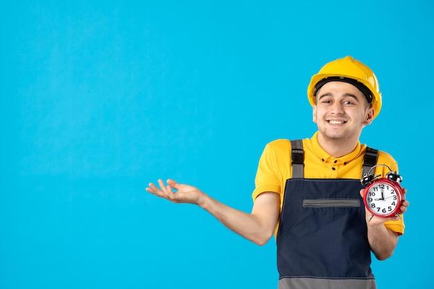 Vorderansicht des lächelnden männlichen arbeiters in der gelben uniform mit uhren auf blau