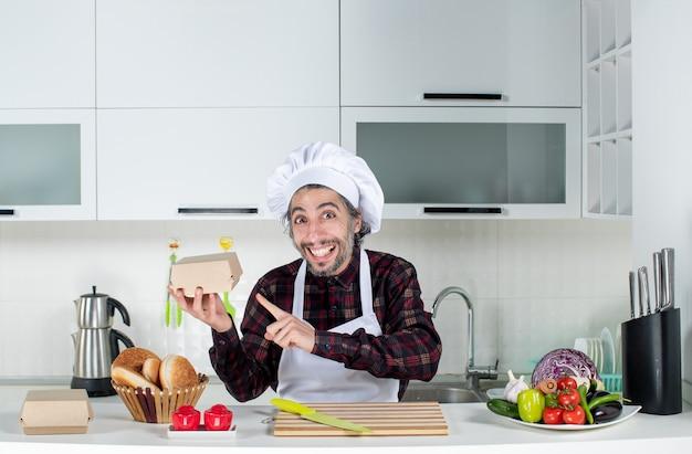 Vorderansicht des lächelnden männlichen kochs, der auf die burgerbox in der küche zeigt