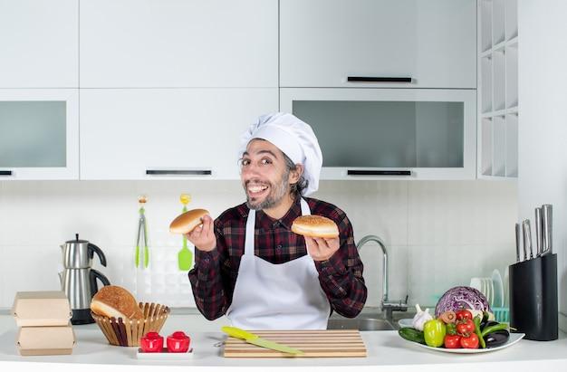 Vorderansicht des lächelnden männlichen kochs, der brot in der küche hält