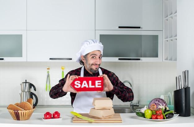 Vorderansicht des lächelnden männlichen kochs, der das verkaufsschild in der küche hochhält