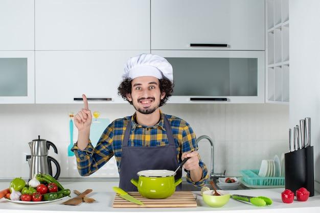 Vorderansicht des lächelnden männlichen kochs mit frischem gemüse, das fertiggerichte schmeckt und in der weißen küche nach oben zeigt