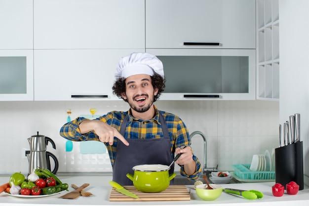 Vorderansicht des lächelnden männlichen kochs mit frischem gemüse und zeigender mahlzeit in der weißen küche
