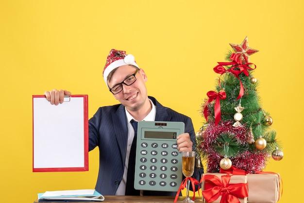 Vorderansicht des lächelnden mannes mit der weihnachtsmütze, die am tisch nahe weihnachtsbaum sitzt und auf gelb präsentiert