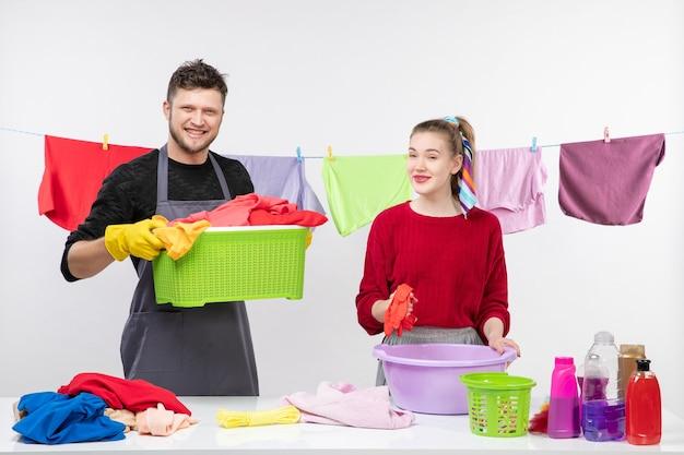 Vorderansicht des lächelnden mannes und seiner frau, die wäschekorb und plastikwaschwanne halten, die hinter tischwäschekörben stehen und sachen auf dem tisch waschen