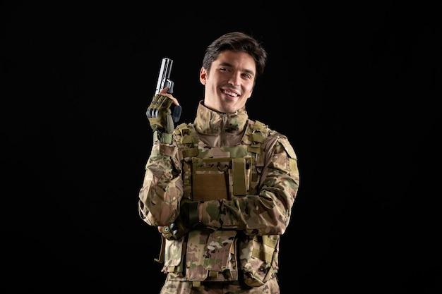 Vorderansicht des lächelnden militärs in uniform auf schwarzer wand