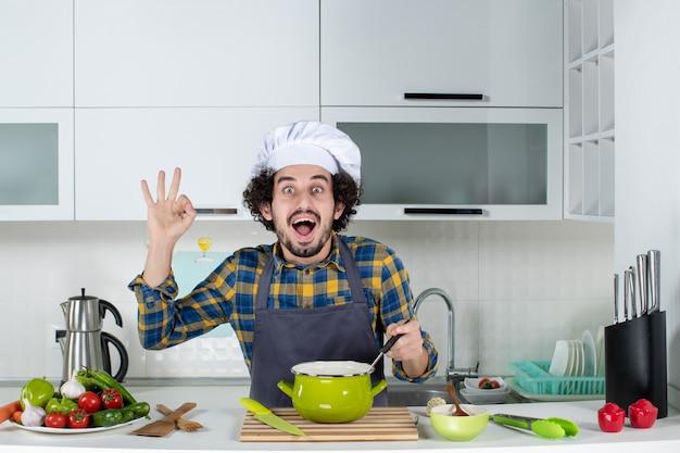 Vorderansicht des lächelnden und glücklichen männlichen kochs mit frischem gemüse, das fertiggerichte schmeckt und in der weißen küche eine brillengeste macht