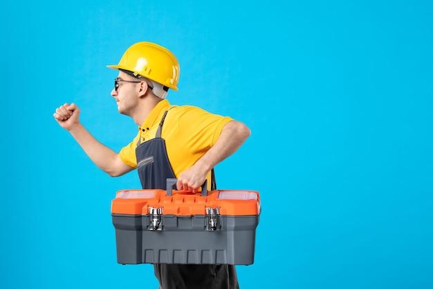 Vorderansicht des laufenden männlichen baumeisters in uniform mit werkzeugkasten in seinen händen auf blau
