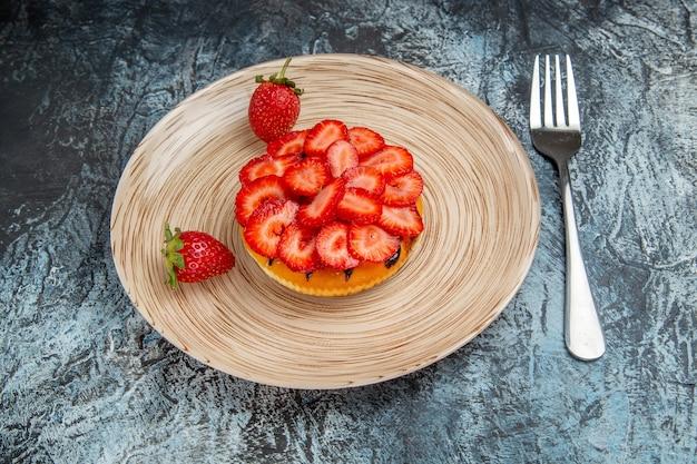 Vorderansicht des leckeren kuchens mit frischen erdbeeren auf dunkler oberfläche