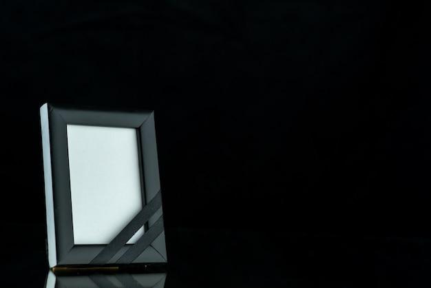Vorderansicht des leeren bilderrahmens auf dunkelheit