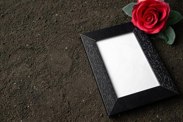 Vorderansicht des leeren bilderrahmens mit roter blume auf schwarz
