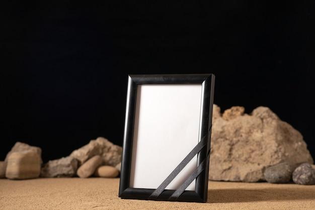 Vorderansicht des leeren bilderrahmens mit verschiedenen steinen auf dunkelheit