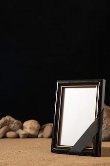 Vorderansicht des leeren bilderrahmens mit verschiedenen steinen auf schwarz