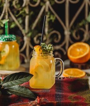 Vorderansicht des limonadengetränks mit geschnittener orange und zitrone, verziert mit minze im cocktailglas mit griff und strohhalm auf einer tischdecke