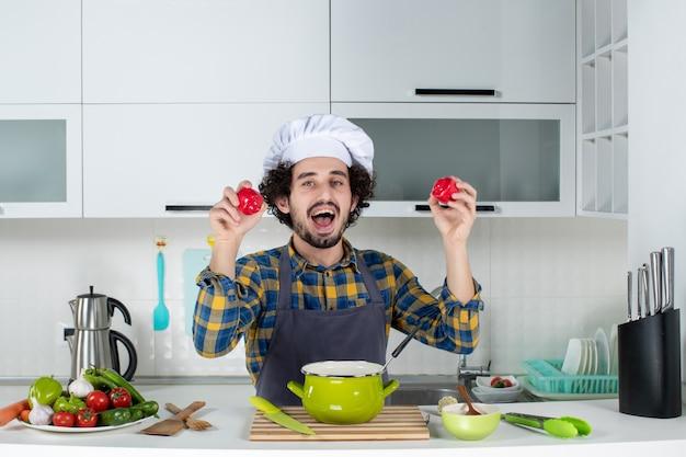 Vorderansicht des lustigen und emotionalen männlichen kochs mit frischem gemüse, das rote paprika in der weißen küche hält