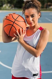 Vorderansicht des mädchens, das basketballball hält