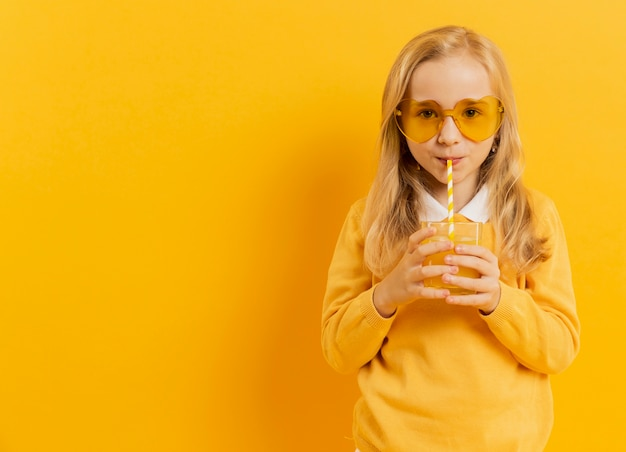 Vorderansicht des mädchens, das beim trinken des saftes und beim tragen der sonnenbrille aufwirft