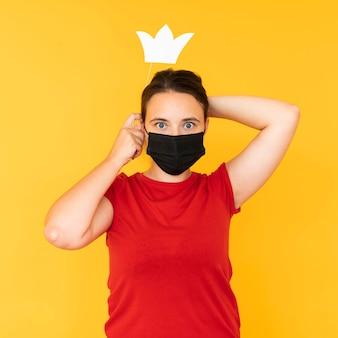 Vorderansicht des mädchens, das eine krone mit gesichtsmaske trägt