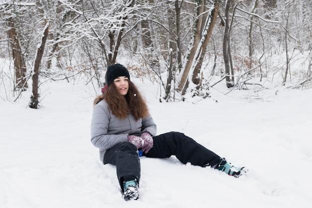 Vorderansicht des mädchens die warme kleidung tragend, die auf schnee sitzt