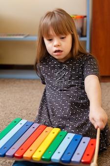 Vorderansicht des mädchens mit down-syndrom, das mit xylophon spielt