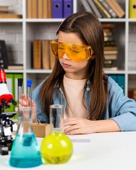 Vorderansicht des mädchens mit schutzbrille und reagenzgläsern