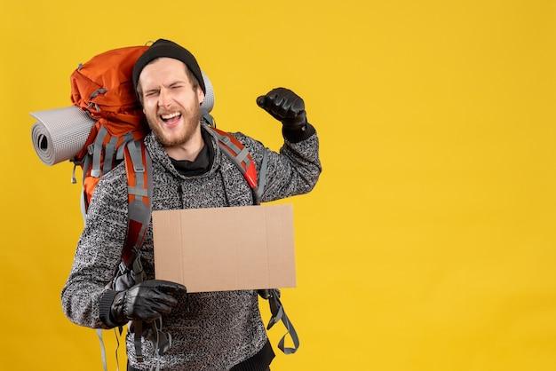 Vorderansicht des männlichen anhängers mit lederhandschuhen und rucksack, der leeren karton hält