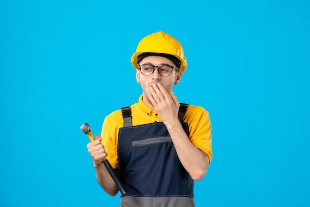 Vorderansicht des männlichen arbeiters in der gelben uniform auf blau