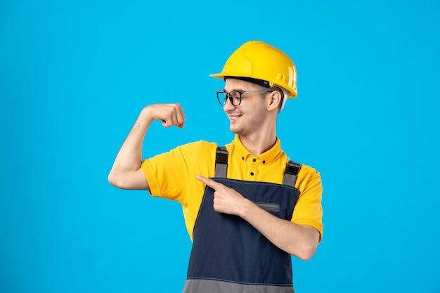 Vorderansicht des männlichen arbeiters in der gelben uniform, die auf blau lächelt und sich biegt