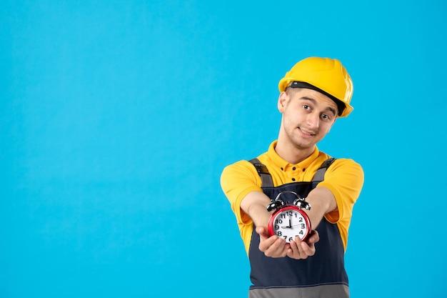 Vorderansicht des männlichen arbeiters in der gelben uniform, die uhren auf blau gibt