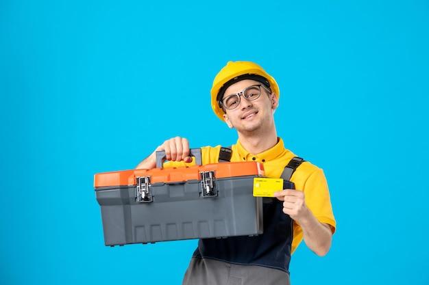 Vorderansicht des männlichen arbeiters in der gelben uniform, die werkzeugkasten auf dem blau trägt