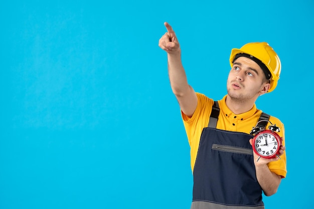 Vorderansicht des männlichen arbeiters in der gelben uniform mit den auf blau zeigenden uhren