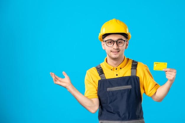 Vorderansicht des männlichen arbeiters in der gelben uniform mit kreditkarte auf blau