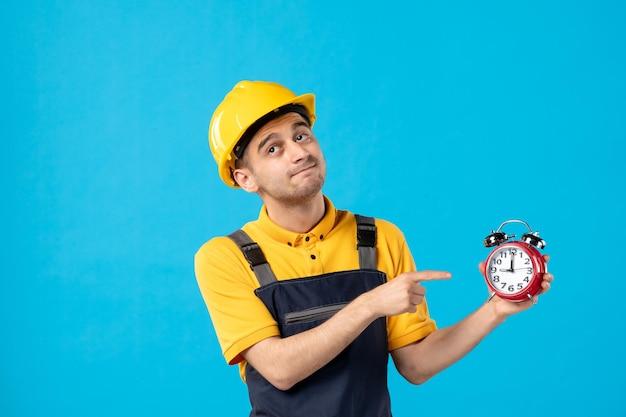 Vorderansicht des männlichen arbeiters in der uniform, die auf uhren auf dem blau zeigt