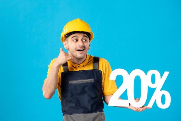 Vorderansicht des männlichen arbeiters in der uniform mit dem schreiben des nachahmenden telefonanrufs auf blau