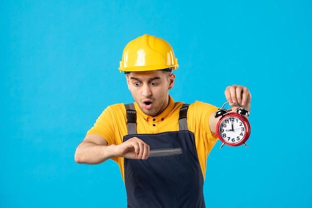 Vorderansicht des männlichen arbeiters in der uniform mit den uhren, die spät auf dem blau sind
