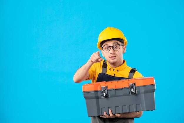 Vorderansicht des männlichen arbeiters in der uniform und im helm mit werkzeugkasten in seinen händen auf blau