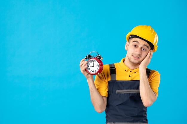 Vorderansicht des männlichen arbeiters in uniform mit uhren in seinen händen auf blau
