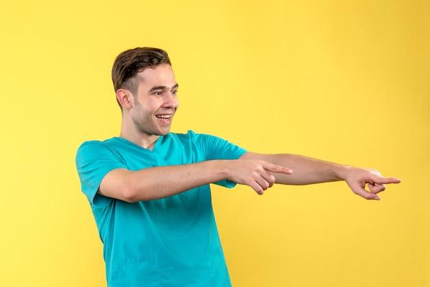 Vorderansicht des männlichen arztes aufgeregt auf gelber wand