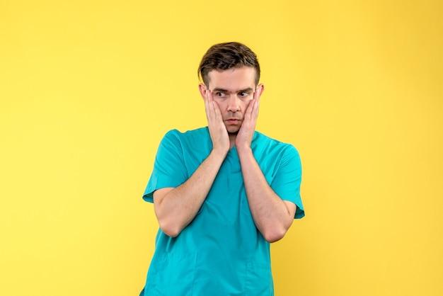 Vorderansicht des männlichen arztes besorgt auf gelber wand