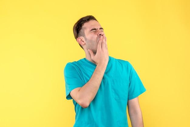 Vorderansicht des männlichen arztes, der auf gelber wand gähnt