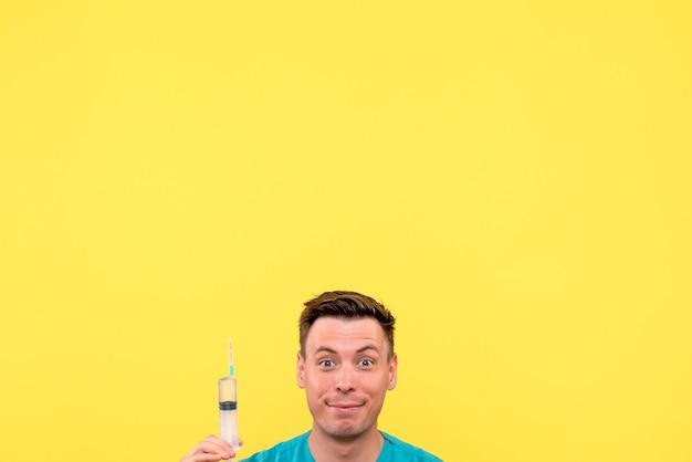 Vorderansicht des männlichen arztes, der große injektion auf gelber wand hält